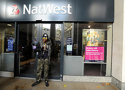 © Licensed to London News Pictures. 24/11/2011, London, UK. A protester leans against the closed branch of Natwest. Protesters with a megaphone cause the closure of a branch of Natwest near to the camp. Occupy UK protest camp at St Paul's Cathedral today 24 November 2011. Photo credit : Stephen Simpson/LNP