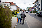 An elderly couple is walking hand in hand during times of social distancing because of the corona virus.