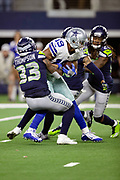 Dallas Cowboys wide receiver Amari Cooper (19) is gang tackled by Seattle Seahawks free safety Tedric Thompson (33) and Seattle Seahawks cornerback Shaquill Griffin (26) as he catches a fourth quarter pass good for a gain of 34 yards and a first down at the Seattle Seahawks 16 yard line during the NFL football NFC wild card playoff game against the Seattle Seahawks on Saturday, Jan. 5, 2019 in Arlington, Tex. The Cowboys won the game 24-22. (©Paul Anthony Spinelli)