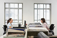 Two women at desks in office side view
