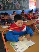 That's one way to control your pupils: Chinese school protects children's eyesight by installing bars that prevent them getting too close to their books <br /> <br /> This primary school in China has given new meaning to the phrase 'raising the bar'.<br /> The institution, in Wuhan, Hubei Province, has literally installed metal bars on to all of its students' desks.<br /> It may not be immediately apparent what the purpose of them is. But teachers have said they will prevent children from 'damaging their eyes' by ensuring they hold their books at an appropriate distance while reading<br /> Headmaster Zhang Jianming, of the Zhang Lin Elementary School, said the bars were installed by the City Teen Anti-Myopia Office.<br /> He explained that they will be used to help children develop good reading habits.<br /> The bars can be moved up and down to stop students moving their heads too close to the books.<br /> The bars can also be pushed back to the distance at which children should be holding their books.<br /> ©Exclusivepix