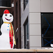 Snowman wearing orange hard hat built at condominium construction project on Queen Anne Hill, Seattle, Washington