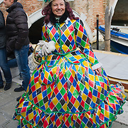 VENICE, ITALY - FEBRUARY 20:  A woman wearing and Arlecchino costume poses for the camera along the Cannaregio Canal during the Venetian Feast on February 20, 2011 in Venice, Italy. During the Venetian Feast a traditional water parade sails from San Marco along the Canal Grande to the  district of Cannaregio where there the crowd waits for the Svolo della Pantegana  (flight of the mouse).