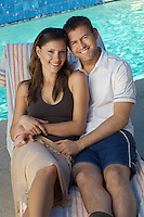 Couple in deck chair by swimming pool, portrait