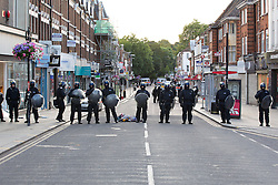 © Licensed to London News Pictures. 07/08/2011. Enfield, UK. Police engage in a tense standoff with youths in Enfield Town Centre. They stop and search some. A police car and local shops have been vandalised. Groups of masked youths hang around the area. Police dogs are deployed. Photo credit : Joel Goodman/LNP