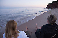 Two women relax on the beach at sunset at Basin Head beach, Prince Edward Island, Canada.
