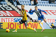 Alex Ravell of Wigan Athletic gets a shot in ahead of Zak Whitbread of Shrewsbury Town during the Sky Bet League 1 match at the DW Stadium, Wigan<br /> Picture by Matt Wilkinson/Focus Images Ltd 07814 960751<br /> 21/11/2015