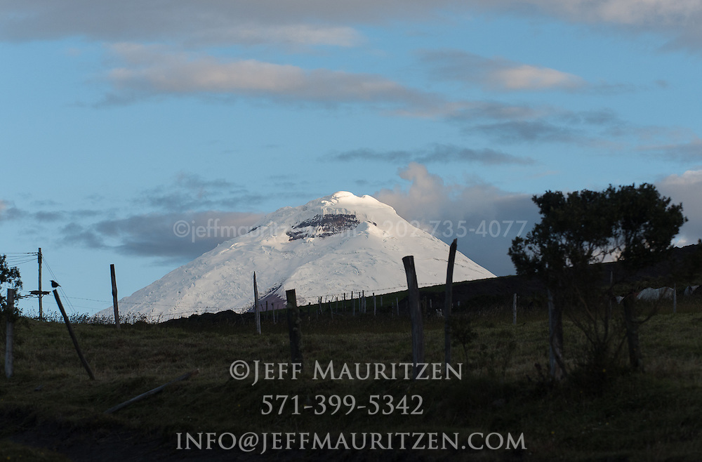 Cotopaxi volcano towers above a nearby ranch at twilight.