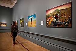 © Licensed to London News Pictures. 17/09/2013. London, UK. A member of gallery staff looks at 'Ned Kelly' (1946) (2 R) and Glenrowan (1970-1) (R), painted by Australian artist Sidney Nolan as part of his iconic series about the Australian outlaw, at the press view for the Royal Academy of Arts latest exhibition 'Australia' in London today (17/09/2013). The exhibition, said to be the most significant survey of Australian art ever mounted in the UK, spans more than 200 years, from 1800 to the present, and runs from the 21st of September to the 8th of December 2013. Photo credit: Matt Cetti-Roberts/LNP