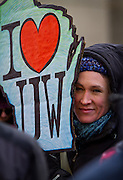 "MADISON, WI — FEBRUARY 13, 2015: A rallygoer holds a sign in support of the University of Wisconsin during the ""Stop the Cuts"" Rally on Library Mall, Saturday, February 14, 2015. The rally drew hundreds of student, faculty and community supporters in spite of the cold Midwest weather."