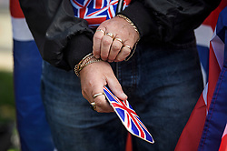 © Licensed to London News Pictures. 19/10/2019. London, UK. A Pro Brexit demonstrator holds a phone with a Union Flag cover outside The Houses of Parliament in Westminster, London on the day that Parliament will vote on a new agreement between UK government and the EU over Brexit. Parliament is sitting on a Saturday for the first time since 1982. Photo credit: Ben Cawthra/LNP