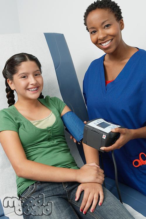 Female nurse taking girls blood pressure in hospital,portrait