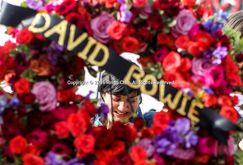 1月11日,在美国洛杉矶,一名歌站在放置在好莱坞星光大道大卫&middot;鲍伊(David Bowie) 星旁的花圈后哭泣。英国传奇歌手大卫鲍伊与病魔抗争18个月后今天病逝,享寿69岁。新华社发 (赵汉荣摄)<br /> A woman cries behind a wreath at the Hollywood Walk of Fame star of David Bowie in Los Angeles, Monday, Jan. 11, 2016. Bowie, the other-worldly musician who broke pop and rock boundaries with his creative musicianship, nonconformity, striking visuals and a genre-spanning persona he christened Ziggy Stardust, died of cancer Sunday. He was 69 and had just released a new album. (Xinhua/Zhao Hanrong)(Photo by Ringo Chiu/PHOTOFORMULA.com)<br /> <br /> Usage Notes: This content is intended for editorial use only. For other uses, additional clearances may be required.