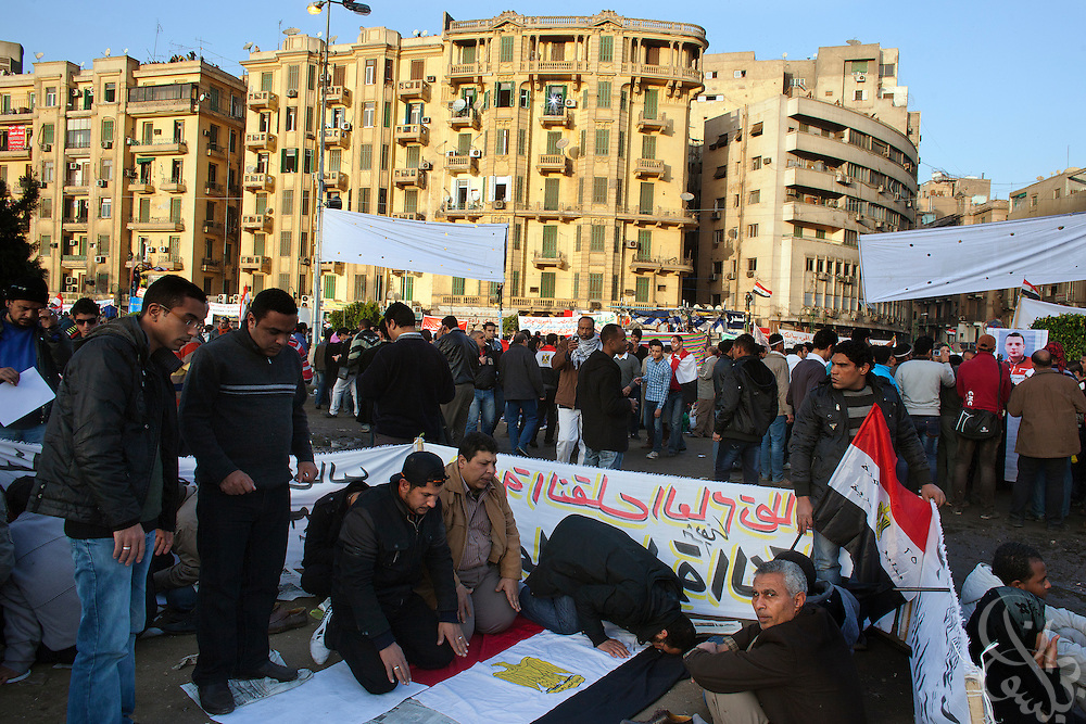 Egyptian Islamists pray on an Egyptian flag during celebrations and protests marking the anniversary of the Egyptian revolution in Tahrir Square January 25, 2012 in Cairo, Egypt.