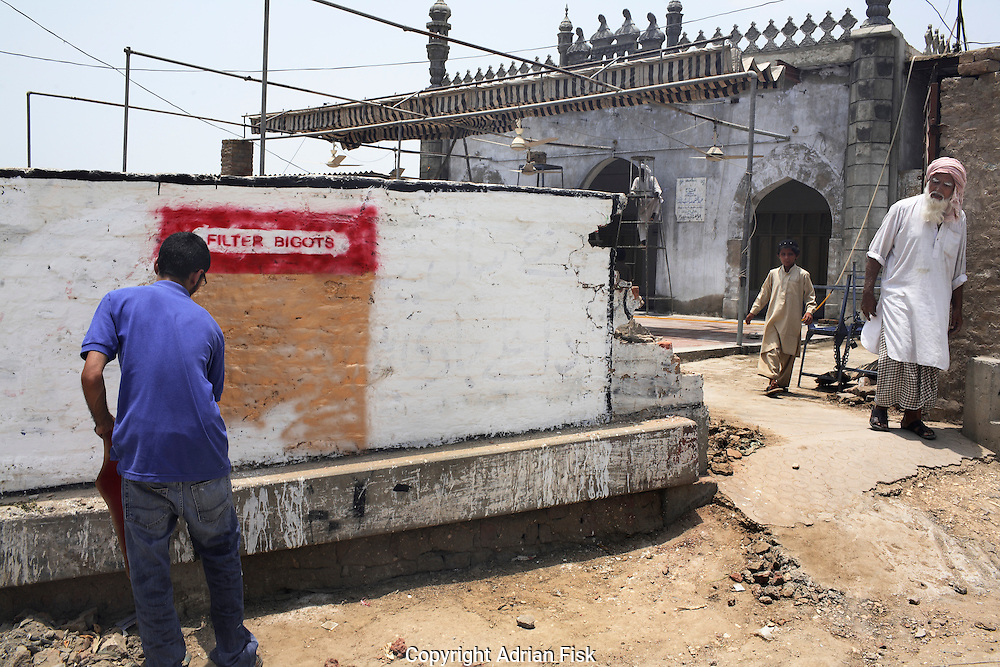Celebrated young pakistani artist Asim Butt on a journey of political graffiti through Pakistan during the summer of 2009..On a mosque wall in Sakkur Asim works on the piece 'Filter Bigots' which talks about the deception of religion and addiction to it, text from cigarette packaging and the Pakistan legal code for fraud, 420.