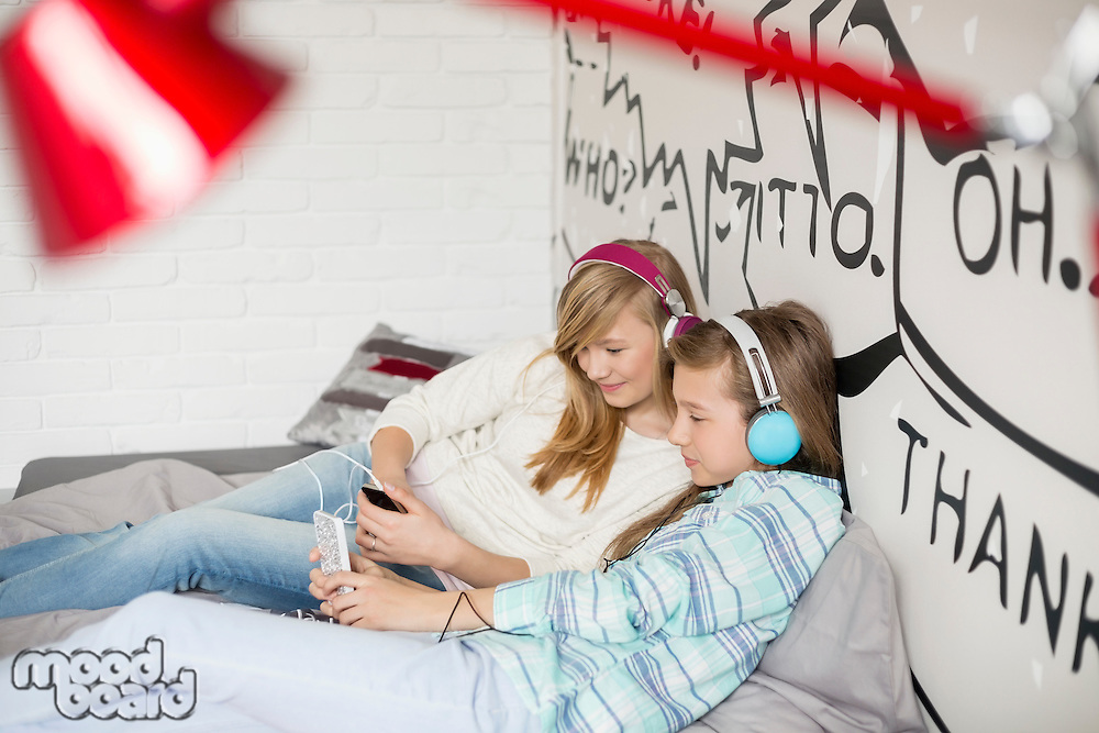 Relaxed sisters listening to music at home