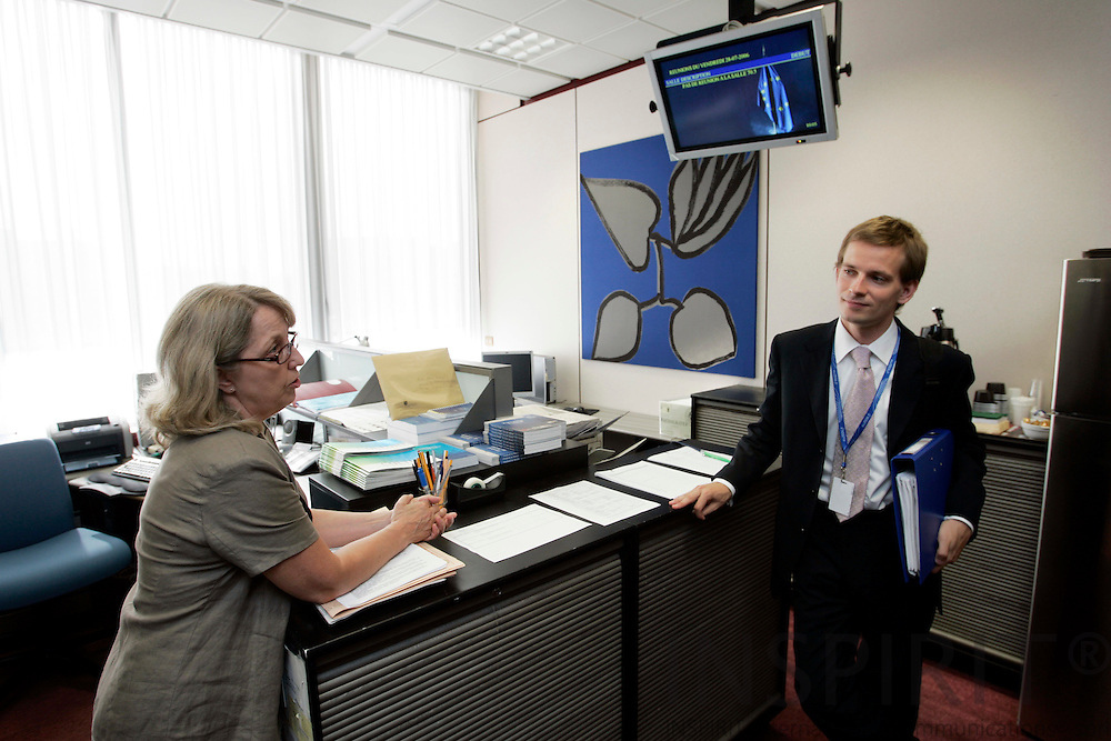 BRUSSELS - BELGIUM - 28 JULY 2006 -- Lauri VOIONMAA, Attache Foreign Relation Counsellors, the Permanent Representation of Finland to the EU speaking with Kaija AHO, assistant, at her office in the EU Council. -- PHOTO: ERIK LUNTANG / ..
