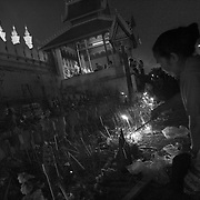 A devotee lights a candle at Pha That Luang in Vientiane, Laos.
