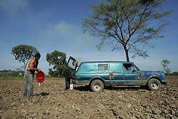 "Men water a watermelon field on the El Charcote cattle ranch  where they are squatting with hundreds of other people. The Venezuela government recently began a three month ""intervention"", during which they will evaluate the productivity of the land on the British owned cattle ranch.  If the government determines the lands to be under-producing, or that the proper titles are not in order, they may redistribute those lands to the poor farmers who have been squatting on the lands."