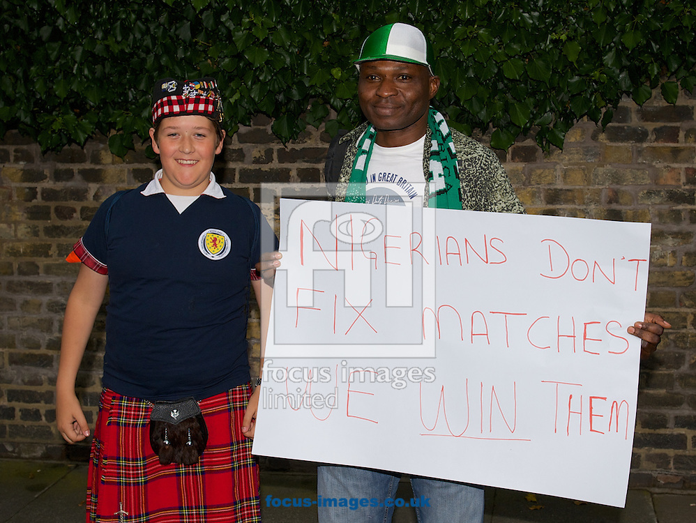 A Nigerian fan with a banner relating to the match fixing with a scottish fan before the International Friendly match at Craven Cottage, London<br /> Picture by Alan Stanford/Focus Images Ltd +44 7915 056117<br /> 28/05/2014