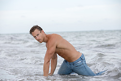 man in wet jeans in the ocean