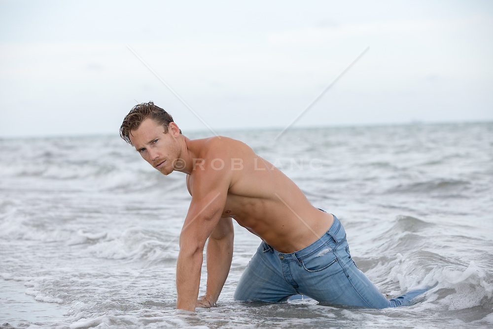 man in wet jeans in the ocean