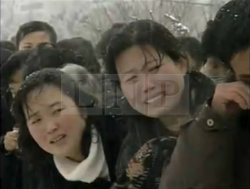 © licensed to London News Pictures. London, UK  28/12/2011. CAPTURE FROM NORTH KOREAN STATE TELEVISION AS STREAMED LIVE ON INTERNET. Shots of people wailing in the snow are shown on North Korean state television during the funeral procession of the State's former leader, Kim Jong-il. The sound of wailing citizens and the funeral band leading the procession is played over the footage. Please see special instructions for usage rates. Photo credit should read Joel Goodman/LNP