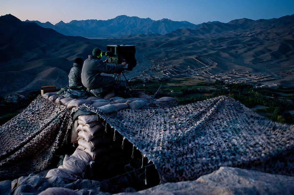Specialist David Burdette looks through a high-powered night vision device at the road below, trying to spot Afghan insurgents laying IEDs.
