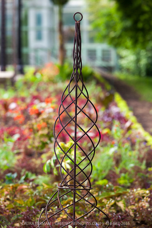 A spiral wrought iron climbing plant support adds a formal note to a garden bed.