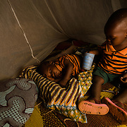 Twins, Lassane and Adama Ouedraogo (2), under the mosquito net they share with their mother, Kadigueta Ouedraogo (29), in the village of Songodin in the Sanmatenga region of Burkina Faso on 25 February 2014. Mosquito nets greatly decrease the incidence of malaria by reducing the risk of being bitten by the nocturnal Anopheles mosquito, which carries the malaria parasite.