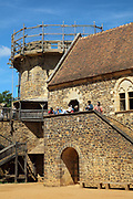 Visitors on the staircase leading to the main hall of the North Range or Logis Seigneurial, completed in 2010, with the Chapel Tower behind, at the Chateau de Guedelon, a castle built since 1997 using only medieval materials and processes, photographed in 2017, in Treigny, Yonne, Burgundy, France. The Guedelon project was begun in 1997 by Michel Guyot, owner of the nearby Chateau de Saint-Fargeau, with architect Jacques Moulin. It is an educational and scientific project with the aim of understanding medieval building techniques and the chateau should be completed in the 2020s. Picture by Manuel Cohen
