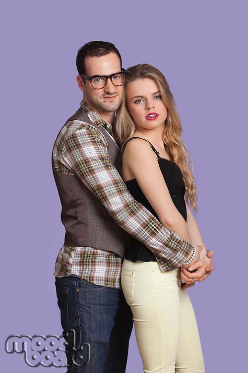 Portrait of romantic young couple against purple background