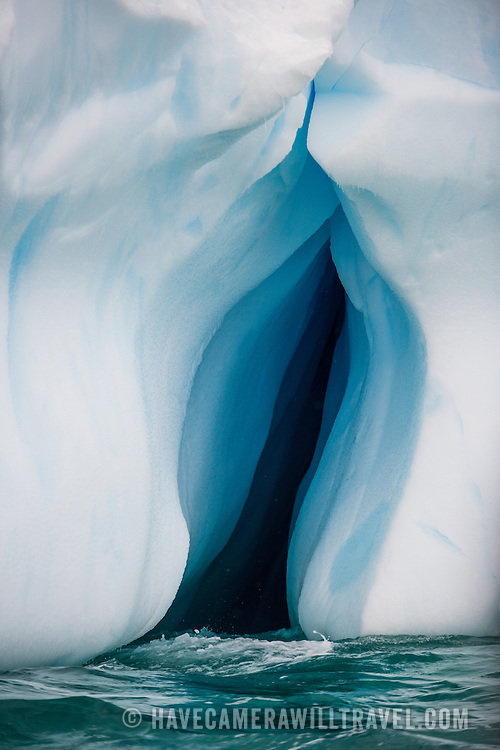 An inverted crevice carved into an iceberg floating on the waters of Curtis Bay, Antarctica