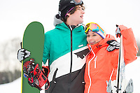 Young couple with snowboard and skis in snow