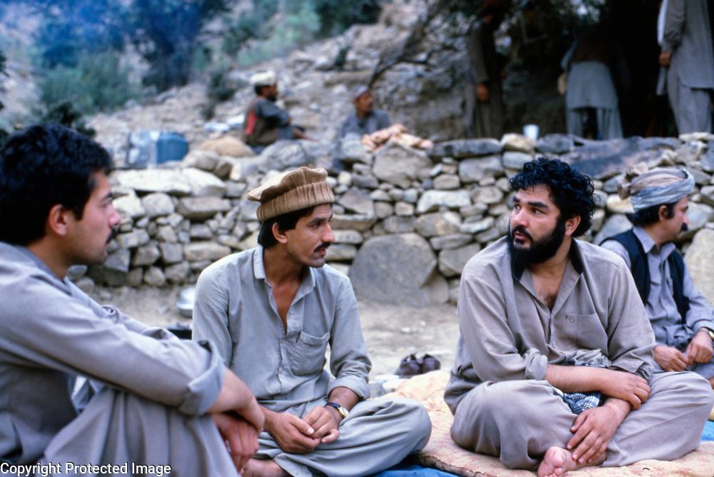25 July 1985<br /> Cooking meal in background. Left Mohd. Gailani, son of Pir Gailani. Babrakzai on right. Bearded chap is Wakil Akbarzai. Mohd. Gailani's bodyguard in rear center.