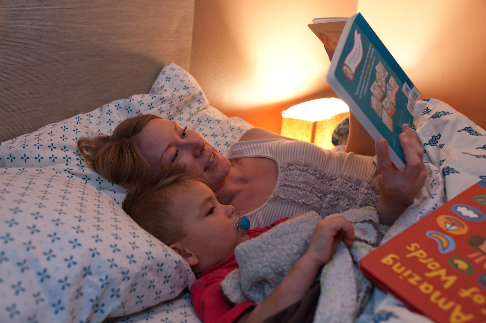 mother reading book to young son, both lying in bed