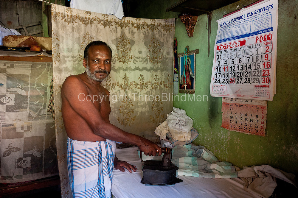 The laundryman or 'dhobi' ironing clothes with a charcoal fired iron.