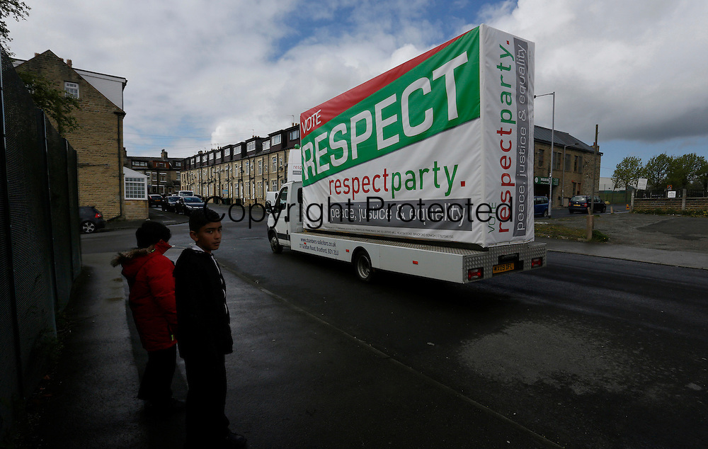 Two boys watch as a van carrying a Respect Party banner drives by.