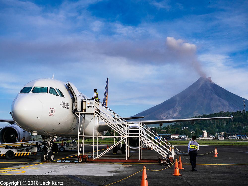 01 FEBRUARY 2018 - LEGAZPI, ALBAY, PHILIPPINES: Philippine Express Airlines flight 2922, an Airbus A320, waits to depart the Legazpi airport with Mayon volcano in the background. The Mayon volcano started erupting in the middle of January. The airspace around the volcano has been closed off and on for more than week. The airport is about 13 kilometers from the volcano and the ash clouds from Mayon pose a threat to aircraft engines. More than 80,000 people have been evacuated from their homes around the volcano.     PHOTO BY JACK KURTZ