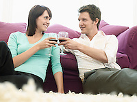 Young couple relaxing on sofa toasting with wine