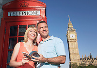 Couple with guidebook standing by London phone booth