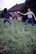 Alvin and Neville play sword fighting at Hawthorne Road, High Wycombe, UK, 1980s.