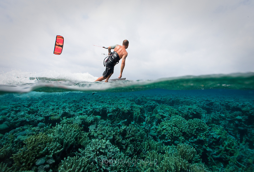 Kiteboarder glides effortlessly over untouched perfect coral garden in the Marshall Islands, Micronesia.
