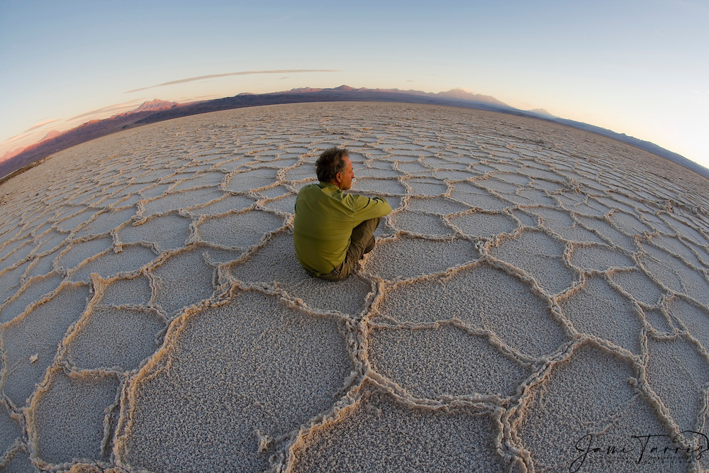 """Man sitting on hexagons in dry salt lake """"Salar de Atacama"""", the largest salt lake in Chile, the northern part has a flamingo reserve, while there is a salt mining operation in the south,Atacama Desert,Chile,South America"""