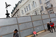 "A couple walk past a temporary construction hoarding beneath the partially hidden statue of the world famous London Victorian-era landmark, Eros in Piccadilly Circus, on 25th February 2020, in London, England. Eros, or the Shaftesbury Memorial Fountain is located at the southeastern side of Piccadilly Circus in London, United Kingdom. Moved after World War II from its original position in the centre, it was erected in 1892–1893 to commemorate the philanthropic works of Lord Shaftesbury, who was a famous Victorian politician and philanthropist. The monument is surmounted by Alfred Gilbert's winged nude statue generally, though mistakenly, known as Eros. This has been called ""London's most famous work of sculpture."""