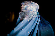 Afghanistan: 28 year old Palwasha prepares to go out to the city wearing in her blue burqa...A wife and mother of 3 boys and 3 girls, she says her husbands daily wage, as a daily labourer of 100Afs (US$2.30) per day is not sufficient for feeding her family. She says her husband leaves the family home at 07.00am every morning returning after nightfall...Her husband occasionally buys  a bulk lot of plastic bags for 10Afs,  which are then divided and sold individually for 5 Afs each by her sons in Kabul city centre. ..Palwasha says she and her family returned from Iran some 7 years ago after fleeing heavy flighting in Kabul in late 1998...She says she sometimes receives help from NHO's such as UNHCR, supplying charcoal during the winter months and NFI's...Afghans returning from exile abroad face many challenges. Security is a major obstacle to return in many districts. Others choose not to return tot heir villages because of landlessness or the lack of job opportunities, fuelling population movements and especially further urbanisation. Impoverished returnees and IDP's living in Kabul cit struggle to meet their daily needs. The attraction of daily wage labour draws growing numbers to the city. But the rising cost of rental accommodation and basic commodities price them out of the market and relegate them to life in the informal settlements which have mushroomed across the city...While 70-80% of kabul city os considered as 'informal' in the sense it is not covered by the Kabul Master Plan, UNHCR's focus is on a limited number of highly documented such 30 sites dotting the city which are home to over 2,000 families. Some families are living under canvas and the constant threat of eviction. others have gained a toe-hold in abandoned around building in the city...Afghanistan/UNHCR/Jason Tanner/February 2011