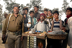 An Indian police officer and villagers selling Betel nut also called Paan pose for a photo.  Chewing is a part of many Asian and Pacific cultures  and  after about 20 minutes of chewing, the fibrous residue which remains of the nut is spat on the street, where it remains visible due to its characteristic bright red pigment. Trails of bright red spit lining the sidewalks are a sure indication of the popularity of betel chewing in an area.