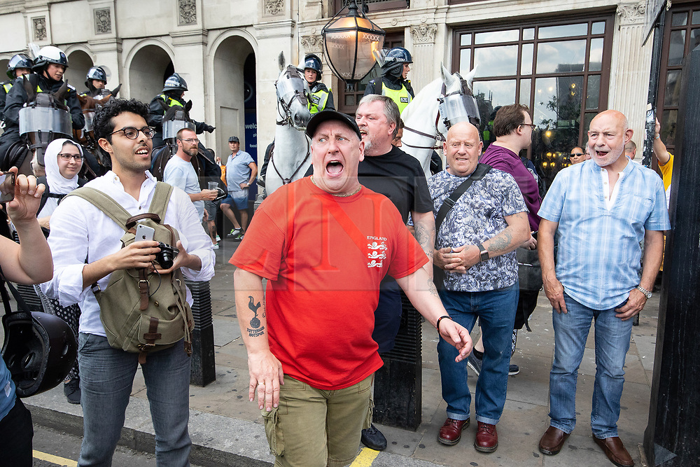 © Licensed to London News Pictures. 14/07/2018. London, UK. PICTURED CENTRE AND RIGHT: Pro Trump/Robinson supporters . Supporters of EDL founder Tommy Robinson ( real name Stephen Yaxley-Lennon ) and US President Donald Trump and anti fascists clash on Westminster Bridge during a day of demonstrations and rallies in support and opposed to US President Donald Trump and jailed EDL founder Tommy Robinson . Trump is currently in Scotland and Robinson is in HMP Hull . Photo credit: Joel Goodman/LNP