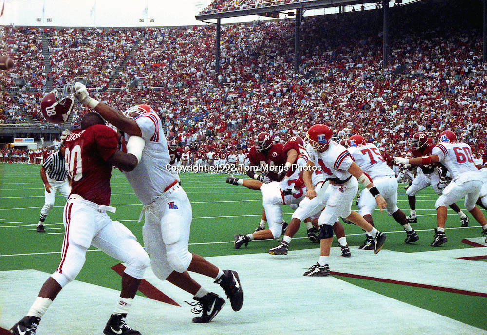 Louisiana Tech offensive guard Willie Roaf tears off the helmet off of all-time Alabama right defensive end Eric Curry (80), while blocking for QB Sam Hughes on a play during Tech's Sept. 26, 1992 game with the Crimson Tide at Legion Field in Birmingham, Ala.   Alabama won the game 13-0, but NFL scouts said his performance in this game solidified Roaf's reputation as a potential high NFL draftee  after going head to head with Curry, a all-America player himself. Roaf was drafted the next spring, 1993, by the New Orleans Saints. He ended his playing career with the Kansas City Chiefs.<br /> <br /> This picture appeared in SPORTS ILLUSTRATED year-end issue for 1993 in a feature story about Willie Roaf.<br /> Photo (c)1992 by<br /> Tom Morris/www.tommorrisphotos.com<br /> (This photo appeared in Sports Illustrated year-end double issue December, 1993)