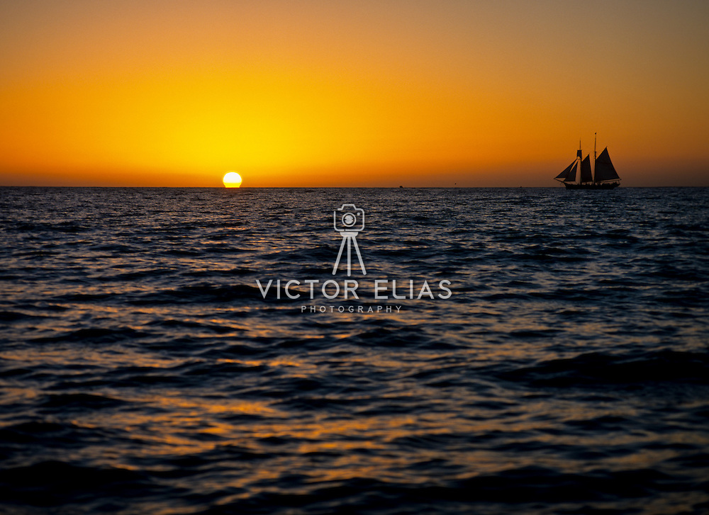 Sailboat navigating into the sunset. Cabo San Lucas, Baja California Sur. Mexico.